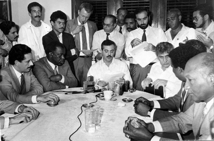Hatuey De Camps, José Francisco Peña Gómez, Rafael Alburquerque (de pie), Cor. (r) Miguel A. Hernando Ramírez (de pie), Luis Armando Asunción (de pie, detrás), Anís Vidal Dauhajre, Andrés Dauhajre hijo (de pie), Jacobo Majluta y Amadeo Lorenzo, en la reunión de la firma del acuerdo entre José Francisco Peña Gómez y Jacobo Majluta para la participación de ambos en la convención para elegir el Candidato Presidencial del PRD para las elecciones generales de 1990, en las cuales participarían también Joaquín Balaguer por el PRSC y Juan Bosch por el PLD. La Comisión Mediadora por la Unificación del PRD integrada por Jesús Feris Iglesias, Anís Vidal Dauhajre, Alberto Santana, José Israel Cuello, Rafael Alburquerque, Frank R. Rainieri, Cor. (r) Miguel A. Hernando Ramírez y Andrés Dauhajre hijo. La reunión y firma del acuerdo se celebró en la casa de Jesús Feris Iglesias, el 17 de febrero de 1989.